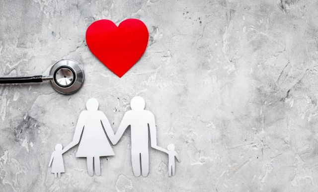 Take out health insurance for family. Stethoscope, paper heart and silhouette of family on grey stone background top view copyspace